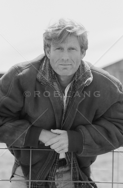 Blond man in a fall jacket looking at camera