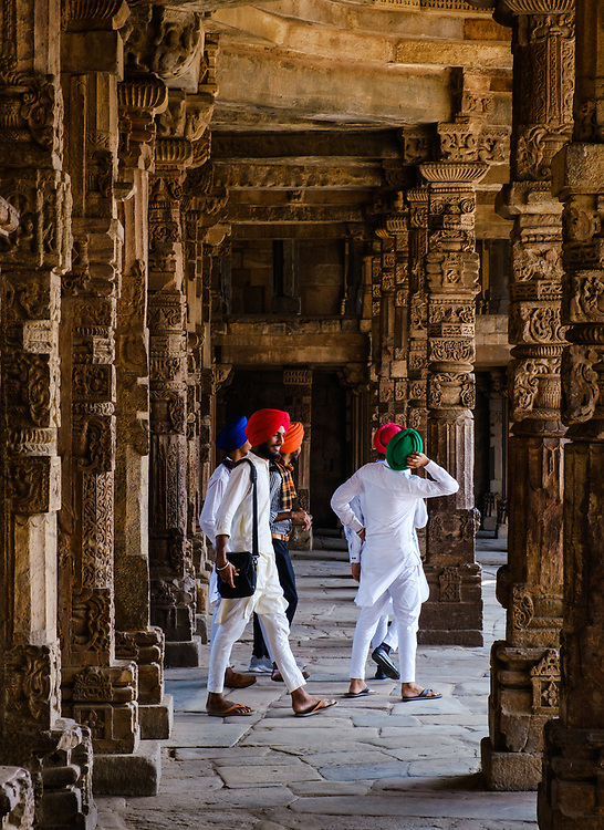 NEW DELHI, INDIA - CIRCA NOVEMBER 2018: Locals walking around Intricate stone carvings on the cloister columns at Quwwat ul-Islam Mosque of the Qutb Minar Complex. The complex features is an array of monuments and buildings at Mehrauli in Delhi, India. An Unesco World Heritage Site and popular touriest attraction in Delhi.