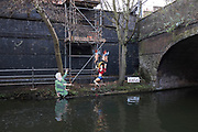 Amy Winehouse is blessed by a kneeling man while cherubs fly her up towards heaven. Joke characters under a bridge on Regents Canal, London, UK.