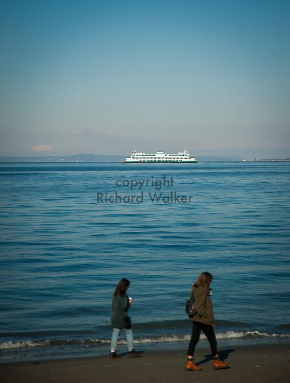 2017 NOVEMBER 06 - People walk on Alki Beach with Washington State Ferry in Puget Sound, Seattle, WA, USA. By Richard Walker