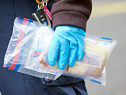 © Licensed to London News Pictures. 27/08/2018. LONDON, UK. A police officer caries an evidence bag containing bloood stained rolls of money, at the scene on Regent Street where a car has crashed into the Hunters shop. The incident is believed to have occurred while it was being chased by police and a pedestrian was injured. IN THIS PICTURE: A police woman carrying a evidence bag that appears to contain blood stained 20 pound notes.  Photo credit: Cliff Hide/LNP