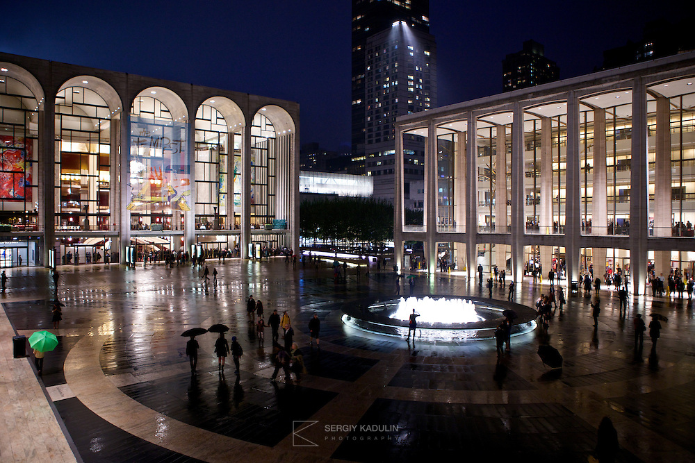 Night view of New York City Ballet and Concert Hall. Buildings are reflected in the wet ground after the rain, adding extra light and perspective.