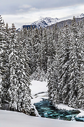 Winter at Hyalite Canyon in the Gallation Mountains near Bozeman Montana.  A half frozen Hyalite Creed winds through the valley bottom.