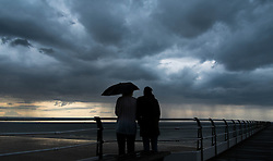 © Licensed to London News Pictures. <br /> 08/06/2014. <br /> <br /> Saltburn, United Kingdom<br /> <br /> Two girls stand and watch from the pier as dark and brooding thunder clouds form over Saltburn, Cleveland.<br /> <br /> Photo credit : Ian Forsyth/LNP