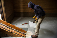 A bit of maneuvering with the ice pick by Alex Chelstowski to fill all the slots in the base row of the Deephaven Ice House on Thursday afternoon.   (Karen Bobotas/for the Laconia Daily Sun)