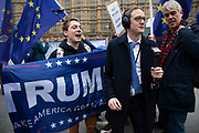 BBC reporter Chris Mason amidst anti Brexit pro Europe demonstrators and one Pro Trump protester waving a Trump - Make America Great Again flag on 4th December 2018 in London, England, United Kingdom.