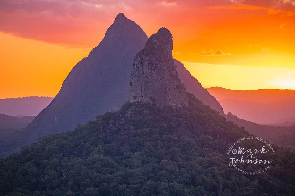 The sun sets behind Mt Coonowrin (fg) & Mt Beerwah, Glass House Mountains, Sunshine Coast, Queensland, Australia