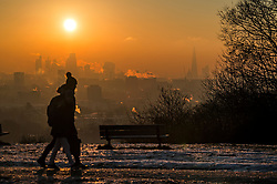 © Licensed to London News Pictures. 12/12/2017. London, UK. Walkers at sun rise on Hampstead Heath in north London as the sun rises over the city of London on a freezing morning. Temperatures across the the UK dipped overnight with some regions expected to drop to -13C (9F). Photo credit: Ben Cawthra/LNP