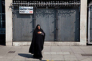 Mislim woman walks past heavily fortified gates on Kentish Town Road, London. Security includes locks, barred doors and anti climb rotating spikes.
