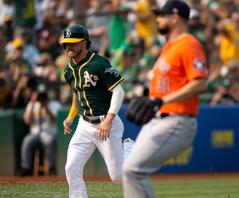 Sep 25, 2021; Oakland, California, USA; Oakland Athletics pinch runner Skye Bolt, left, scores the tying run on a single by Josh Harrison against the Houston Astros during the seventh inning at RingCentral Coliseum. Mandatory Credit: D. Ross Cameron-USA TODAY Sports