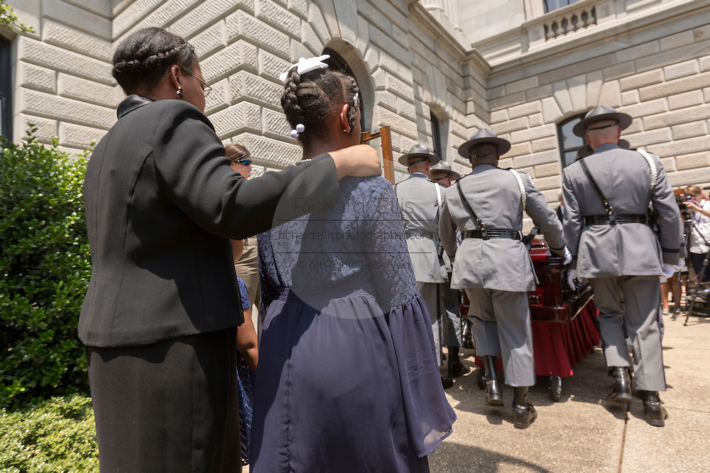 The wife and daughters of slain State Senator Clementa Pinckney are comforted as the casket is carried into the State House by Police honor guard June 24, 2015 in Columbia, South Carolina. Pinckney is one of the nine people killed in last weeks Charleston church massacre.