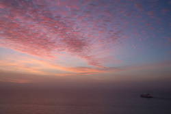 © Licensed to London News Pictures. 23/01/2016.  A cross channel ferry sets off under a gorgeous sky. Sunrise at Dover in Kent seen from the famous White Cliffs. Weather forecasters have predicted a return to mild weather. Credit : Rob Powell/LNP