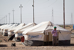 © Licensed to London News Pictures. 25/06/2014. Khanaqin, Iraq. Iraqi refugees are seen at a refugee camp on the outskirts of Bahari Taza village in Iraq. Located on the outskirts of Khanaqin, a town just 20 minutes from the front-line of the battle with ISIS insurgents, the Bahari Taza refugee camp, and its satellite camps, now house around 600 families from southern Iraq. Built by the local village leader to meet the influx of refugees from nearby Jalawla and Saidia, where intense fighting is still taking place. Turkman, Arab and Kurd, both Sunni and Shia, all live together in tents, barns and unfinished buildings waiting for the conflict to end. Photo credit: Matt Cetti-Roberts/LNP