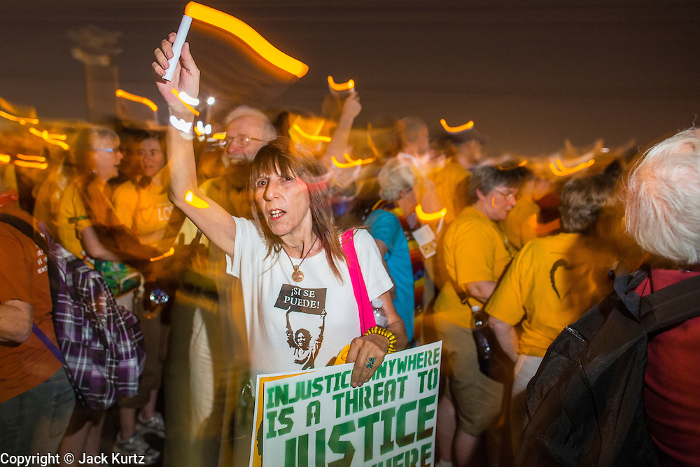 """23 JUNE 2012 - PHOENIX, AZ:  A Unitarian woman carrying an electric candle marches the Maricopa County Jail in Phoenix Saturday. About 2,000 members of the Unitarian Universalist Church, in Phoenix for their national convention, picketed the entrances to the Maricopa County Jail and """"Tent City"""" Saturday night. They were opposed to the treatment of prisoners in the jail, many of whom are not convicted and are awaiting trial, and Maricopa County Sheriff Joe Arpaio's stand on illegal immigration. The protesters carried candles and sang hymns.     PHOTO BY JACK KURTZ"""