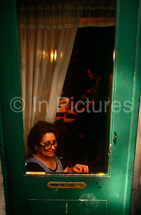 A housewife smiles from her low door in her inner-city home within Lisbon's Bica district of the Portuguese capital. In the shadows a person irons clothes with the help of an electric light bulb. But by her green door in afternoon sunshine, the lady in the foreground looks happy with her lifestyle, darning some material with a good view of passers-by at street level.