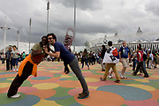 Spectators enjoy the grid-like patterned floor in the Olympic Park during the London 2012 Olympics - a French lady and a friend form a human bridge by leaning at a 45 degree angle with the main stadium as a backdrop. This land was transformed to become a 2.5 Sq Km sporting complex, once industrial businesses and now the venue of eight venues including the main arena, Aquatics Centre and Velodrome plus the athletes' Olympic Village. After the Olympics, the park is to be known as Queen Elizabeth Olympic Park.