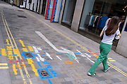 A woman wearing green trousers walks over multi-coloured aerosol-sprayed markings on the ground in a side-street off Long Acre near Covent Garden, are on 23rd June 2021, in Westminster, London, England.