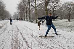 © Licensed to London News Pictures. 24/01/2021. London, UK. A man attempts to skateboard during a snow shower in Greenwich Park. Snow is expected for large parts of the UK and a yellow weather warning is in place in parts of England. Photo credit: George Cracknell Wright/LNP