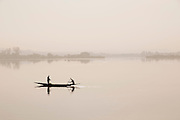 A small fishing boat on the calm Niger River, early in the morning in Bamako, Mali