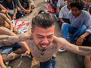 "07 MARCH 2015 - NAKHON CHAI SI, NAKHON PATHOM, THAILAND: A man charges the stage channeling the power of his spiritual tattoo at the Wat Bang Phra tattoo festival. Wat Bang Phra is the best known ""Sak Yant"" tattoo temple in Thailand. It's located in Nakhon Pathom province, about 40 miles from Bangkok. The tattoos are given with hollow stainless steel needles and are thought to possess magical powers of protection. The tattoos, which are given by Buddhist monks, are popular with soldiers, policeman and gangsters, people who generally live in harm's way. The tattoo must be activated to remain powerful and the annual Wai Khru Ceremony (tattoo festival) at the temple draws thousands of devotees who come to the temple to activate or renew the tattoos. People go into trance like states and then assume the personality of their tattoo, so people with tiger tattoos assume the personality of a tiger, people with monkey tattoos take on the personality of a monkey and so on. In recent years the tattoo festival has become popular with tourists who make the trip to Nakorn Pathom province to see a side of ""exotic"" Thailand.   PHOTO BY JACK KURTZ"