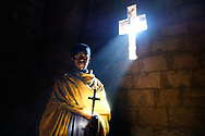 Young priest poses for a portrait under a ray of light inside one of the churches of Lalibela in Ethiopia. Photo by Lorenz Berna