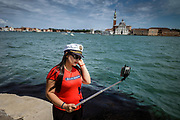 Venice, Italy, 14 may 2018, Woman taking selfies along the canal in Venice
