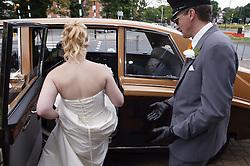 Bride getting into chauffeur driven wedding car,