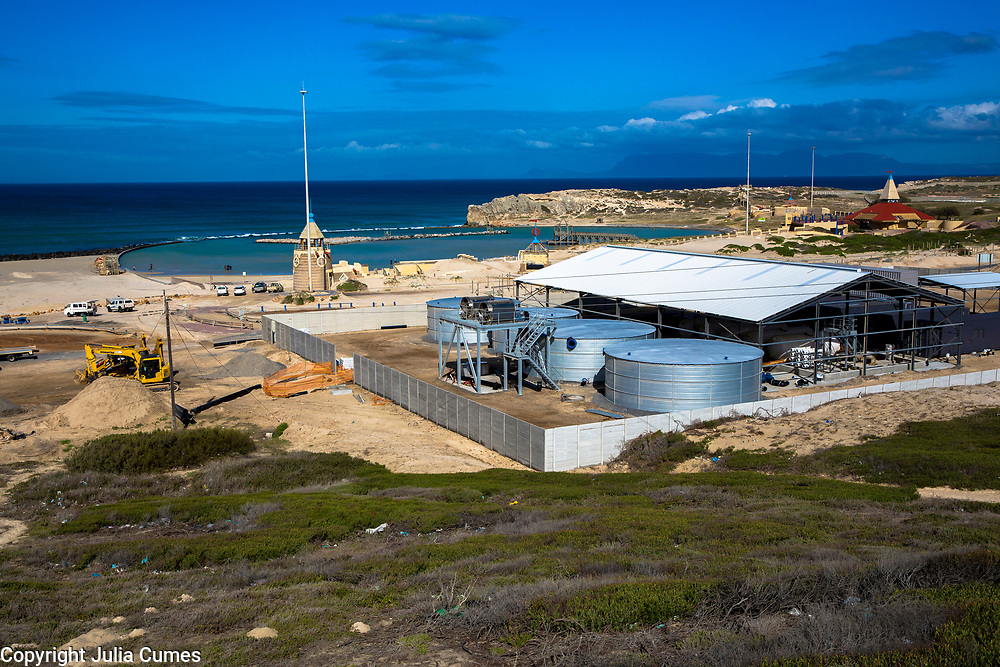 One of multiple private desalinization plants sets up its temporary structure in Monwabisi on Cape Town's False Bay.  The plant, which was erected in a matter of months in reaction to the water crisis and is expected to produce seven million liters of drinkable water per day when it is complete, pulls water out of the ocean 1km out to sea near a popular pool and beach area.