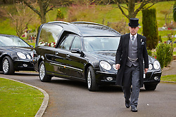 © Licensed to London News Pictures.  14/02/2013. BASINGSTOKE, UK. An undertaker walks in front of the hearse during the funeral of Reg Presley at Basingstoke Crematorium. The lead singer of 1960s rock band The Troggs, who became famous with hits including Wild Thing, died aged 71 earlier this month. Photo credit: Cliff Hide/LNP