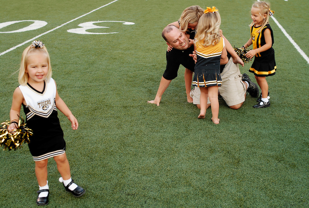 Emma Mallett, 2, looks to her mother as Mike Wheeler, right, is tackled to the turf by (left to right) Mary-Rourke Boyd, 5, Gracie Boyd, 3, and Ellie Mallett, 4.  Fans got the chance to roam Faurot Field during Wednesday's pep rally for the first game against Illinois.