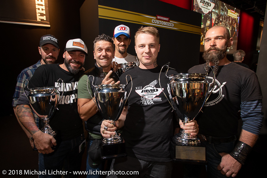 """Ziller's Garage's Dima Golubchikov of Russia with the Italian contingency after Dima got the first place win in the AMD Wolrd Championship of Custom Bike Building for his """"Insomnia"""" custom Yamaha sr400 in the AMD World Championship of Custom Bike Building awards ceremony in the Intermot Customized hall during the Intermot International Motorcycle Fair. Cologne, Germany. Sunday October 7, 2018. Photography ©2018 Michael Lichter."""