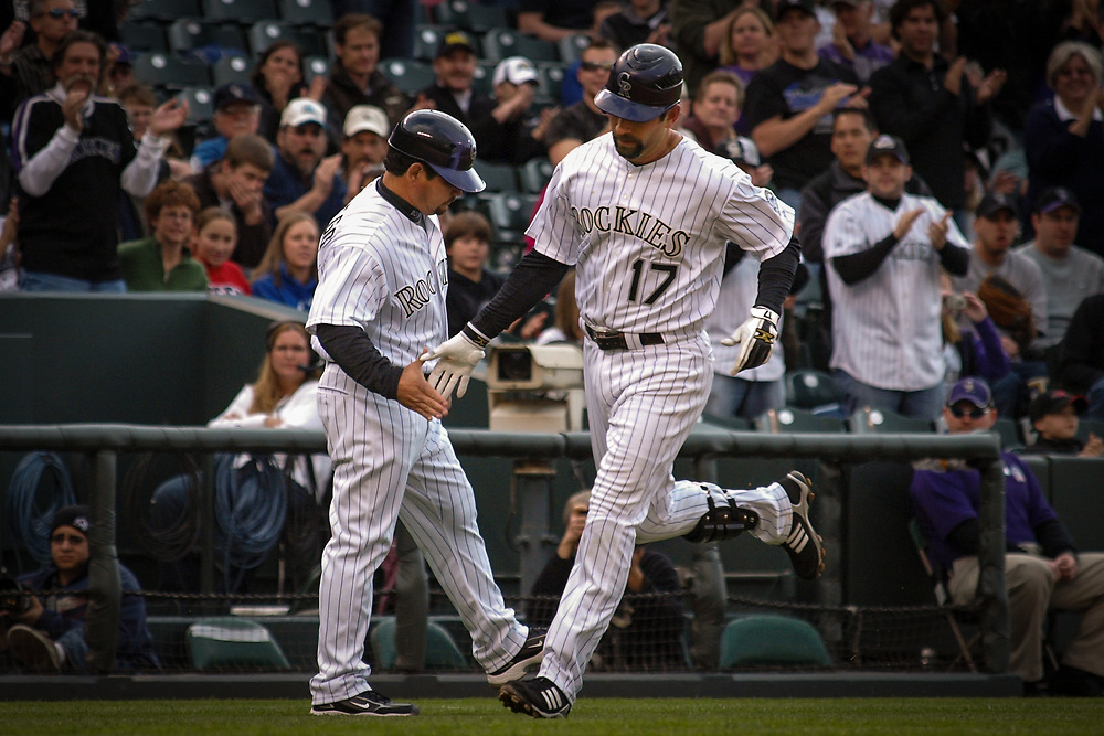 TODD HELTON is congratulated as he rounds third base after hittinbg a home run.