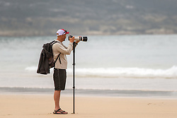 A photographer on Fistral Beach in Newquay, Cornwall.