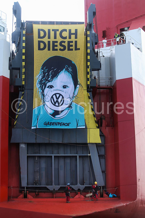 Greenpeace activists have deployed a banner calling VW to ditch dielsel on the back of the cargo ship September 21st 2017, Thames Estuary, Kent, United Kingdom. Greenpeace volunteers in kayaks, speed boats and climbers on the jetty prevent the 23,498-tonne cargo ship Elbe Highway from docking at Sheerness in Kent.  The cargo ship is bringing Volkswagen diesel cars into the UK and the Greenpeace action is to prevent this from happening and to make VW ditch diesel. Two climbers board the ship and hang a banner on the roll-on roll-off part of the ship preventing any cars from being off-loaded. The action is part of a long running Greenpeace campaign to curb diesel emmissions and air pollution brought on by diesel cars.
