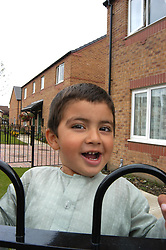 Small boy playing outside his Housing Association home; Halifax; Yorkshire UK