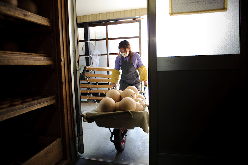 """A worker removes fireworks from the drying room at Katakai Fireworks Co., Ltd, Katakai, Japan, April 6, 2009. The company makes the world's largest firework, a 120cm round shell called a """"yonshakudama""""."""