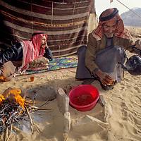 Bedouin men wearing traditional keffiyeh scarves chat and share tea in a wool tent in Jordan's Wadi Rum, part of the Arabian Desert.