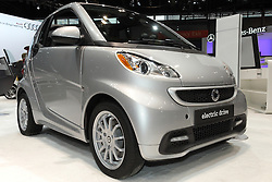 "08  February 2013: Mercedes Benz Smart car. Chicago Auto Show, Chicago Automobile Trade Association (CATA), McCormick Place, Chicago Illinois<br /> <br /> 2013 SMART TWOFOUR: Designed and engineered by Mercedes-Benz, the 2013 Smart ForTwo is a lean, mean, good looking machine. Available in three gasoline-powered models, as well as the fully-electric TwoFour, the Smart provides a solution for environmental efficiency including conservation of material, space and natural resources. Trim levels include the Pure Coupe, Passion Coupe, Passion Cabriolet and Electric Drive model. Powering the 1,808 lb automobile is a one-liter, in-line three-cylinder gasoline engine that creates 70 horsepower to the rear-wheels. The Electric Drive uses a 51-kW electric motor with lithium-ion battery that generates 41 hp. All Smart TwoFour's come mated to a five-speed smartshift transmission with automatic (for ease) and manual (for fun) modes. Cargo room for the two-seater is a surprising 12. cu. ft. Since safety is paramount, the TwoFour comes packed with features including the protective ""tridion safety cell,"" to help ensure crash compatibility with larger passenger cars, plus electronic stability program, anti-lock braking system and eight airbags. There is seven exterior colors to choose from, and two tridon safety cell colors. Interior can be decked out in six different colors, in leather and color upholstery. For the young and young at heart, the TwoFour offers 14 separate, customizable body panel graphics, or you can come up with your own designs and the company will wrap your Smart however you like. Make sure to check-out the Brabus sport package that transform the Smart into a fiercer dream machine with bolder exterior treatment and eye-catching cockpit."