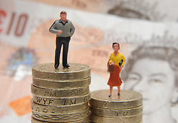 Embargoed to 0001 Wednesday June 28 File photo dated 27/01/15 of plastic models of a man and woman standing on a pile of coins and bank notes. The retirement income gender gap has grown by £1,000 over the last year, a survey has found.