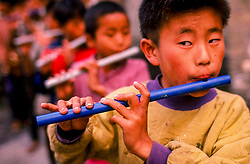 DHARAMSALA, INDIA - OCTOBER 20, 1992 - Children take part in music lessons at a school for Tibetan refugees in Dharamsala, India. The Tibetan children's Village runs a chain of fifteen schools, with over ten thousand students, in different parts of India. The main village, known as the Upper TCV, is based on a hill two kilometres from McLeod Ganj. It educates and looks after the upbringing of about three thousand student, most of whom are orphans and new refugees from Tibet. Upper TCV consists of thirty eight homes, four hostels and a baby room to care for months-old infants through to boys and girls of sixteen. It has modern school buildings ranging from nursery to high school, sports grounds, staff quarters, a dispensary, a handicraft centre, etc. These are spread over an area of about forty three acres. (Photo © Jock Fistick)