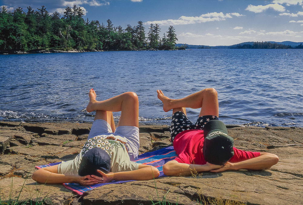 Couple enjoying the sunshine, shore of Squam Lake in summer, Five Finger Point, Sandwich, NH