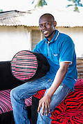 Haji Ally holding a stool and sitting on a recently made sofa. One of the owners of Mnyangu Sofa Seat a local sofa making company, part of the VSO / ICS Elimu Fursa project (Opportunities in Education) Lindi, Lindi region. Tanzania