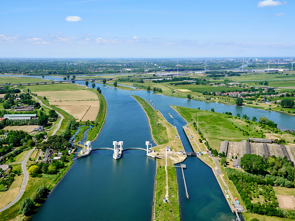 Nederland, Utrecht, Hagestein, 27-05-2020; stuw in de rivier de Lek, dient om het waterpeil in de rivier te reguleren en het scheepvaartverkeer mogelijk te maken. Het gehele stuwcomplex is gerenoveerd. Naast de stuw de schutsluis voor de scheepvaart,vissen kunnen gebruik maken van de de vistrap (vispassage).<br /> Weir in the river Lek, regulates and manages the water level. The Lek is a rain river, with especially in the winter large amounts of water (melt water), in the summer there is a shortage of water, the weir ensures sufficiently high water level for shipping. Next to the dam fish ladder and shipping lock. The complex has being renovated, the visor slides replaced.<br /> <br /> luchtfoto (toeslag op standard tarieven);<br /> aerial photo (additional fee required)<br /> copyright © 2020 foto/photo Siebe Swart