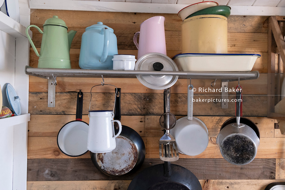 A beach hut interior that includes the furniture, utensils and fittings of its small but well-stocked kitchen, on 25th July 2021, in Whitstable, Kent, England.