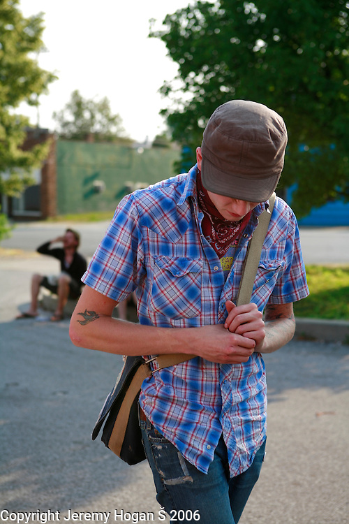 A young man wearing a plaid shirt stands in the parking lot of Rhinos before a punk show at Rhino's All Ages Club in Bloomington, Indiana.