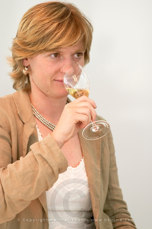 Delphine Geraud, oenologue enologist at the CIVC holding a glass of champagne and tasting it at the Maison de la Champagne (the House of the Champagne Region), the head quarters of CIVC (Comite Interprofessionnel du Vin de Champagne) in Epernay, Champagne, Marne, Ardennes, France