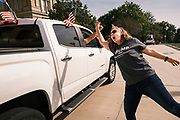 """26 SEPTEMBER 2020 - DES MOINES, IOWA: JANNELL LEFFLER """"high fives"""" people in the motorcade supporting the reelection of President Donald J. Trump as it passes the Iowa State Capitol. More than 1,500 people in 500 vehicles participated in motorcade through Des Moines Saturday. They started in the suburbs south of downtown, drove through downtown, and ended at the State Capitol.      PHOTO BY JACK KURTZ"""