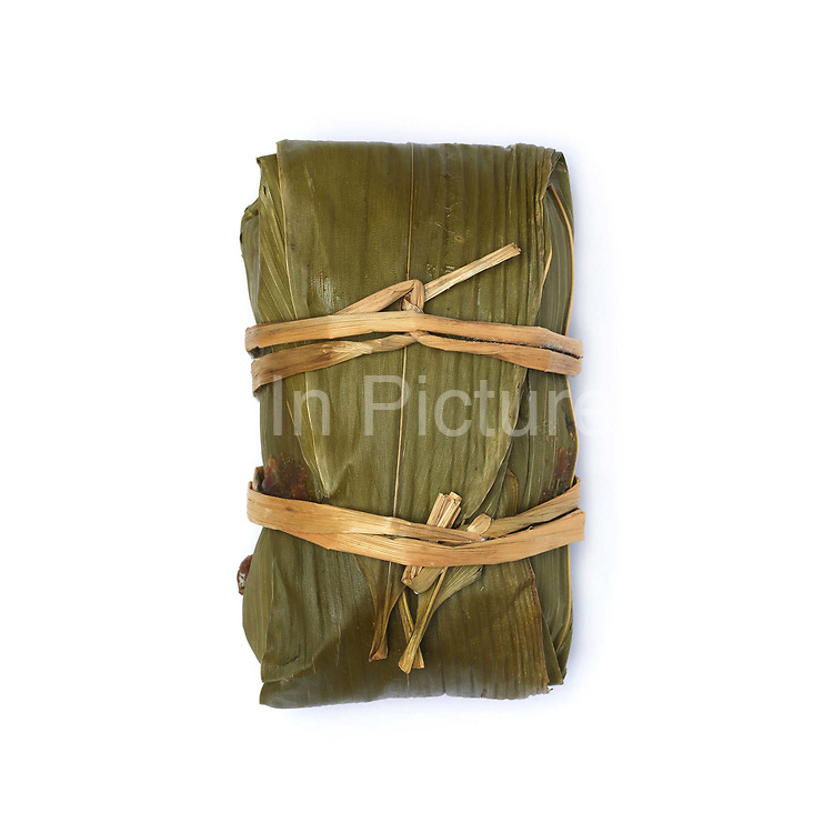 A small sticky rice cake wrapped in leaves from Shui Tang village market; Guizhou province, China.