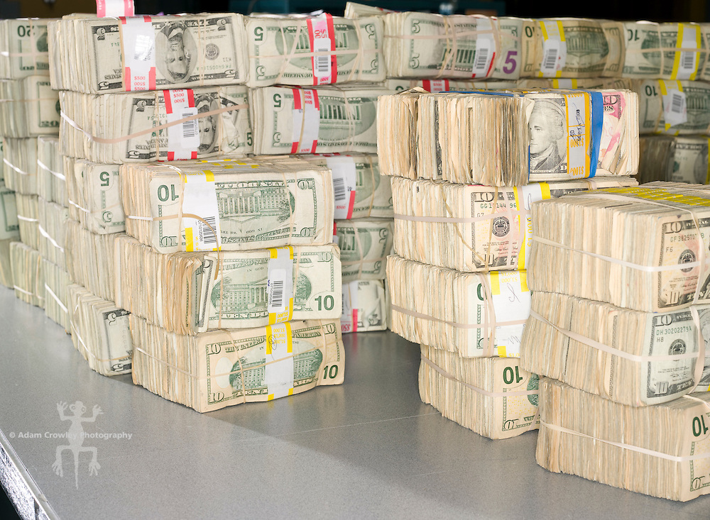 Bundles of various U.S. currency, stacked on a table.