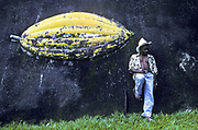 A cocoa worker rests against a wall of a cocoa plantation ranch whilst waiting for a lift, Bahia, Brazil.